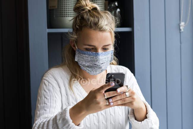 Jeune femme blonde portant un masque facial assise seule dans un café, utilisant un téléphone portable, travaillant à distance. — Photo de stock
