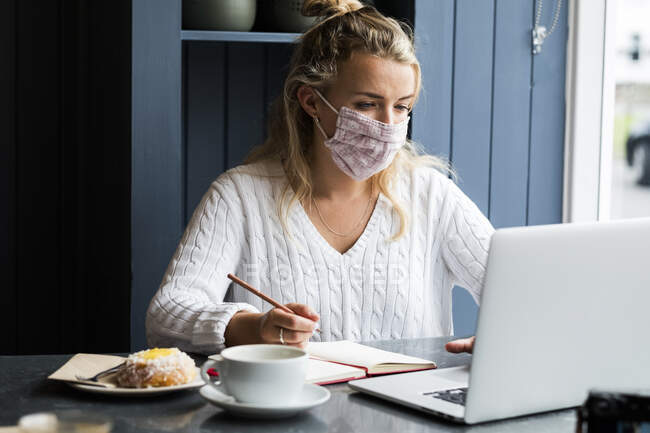 Mulher loira jovem usando máscara facial sentada sozinha em uma mesa de café com um computador portátil, escrevendo em livro de anotações, trabalhando remotamente. — Fotografia de Stock