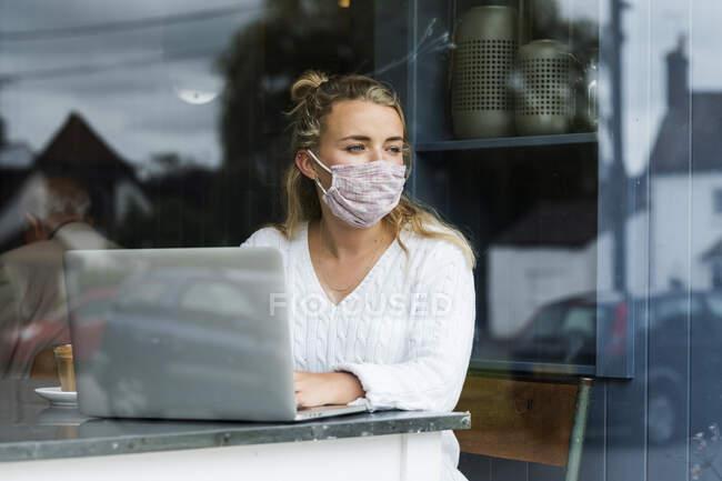 Jovem loira usando máscara facial sentada sozinha em uma mesa de café com um laptop, trabalhando remotamente. — Fotografia de Stock
