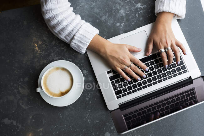 High angle view of woman sitting alone at a cafe table with a laptop, working remotely. — Stock Photo