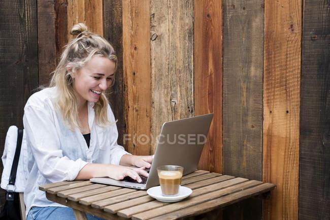 Giovane donna bionda seduta da sola a un tavolo da caffè con un computer portatile, che lavora a distanza. — Foto stock