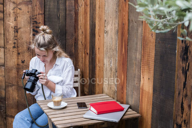 Young blond woman alone at an outdoor table, looking at digital camera display. — Stock Photo