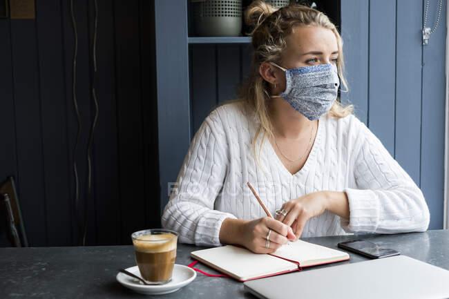 Mulher usando máscara facial sozinha em uma mesa de café com um laptop e notebook trabalhando remotamente. — Fotografia de Stock