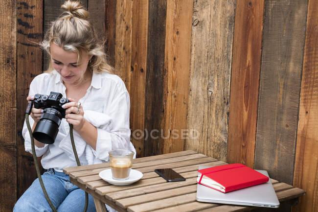 Молодая блондинка одна за открытым столом, смотрит на дисплей цифровой камеры. — стоковое фото