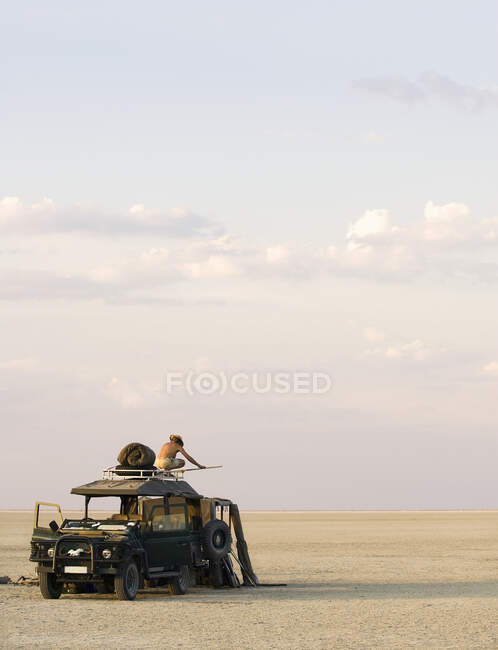 Homem em pé em cima do veículo estacionado nas Panelas de Sal Makadikadi no Botsuana. — Fotografia de Stock