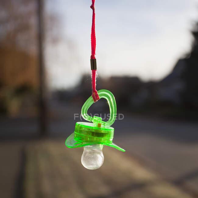 Chupeta de bebê de plástico verde pendurada em um cordão laranja — Fotografia de Stock