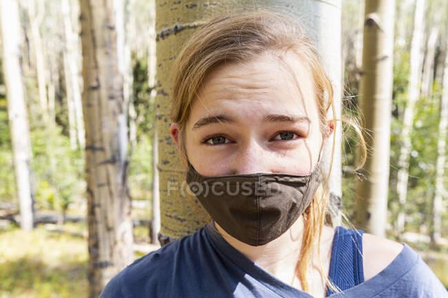 Adolescente portant le masque COVID-19 dans la forêt de trembles — Photo de stock