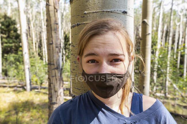 Дівчинка підліткового віку в масці COVID-19 в лісі Аспен. — стокове фото