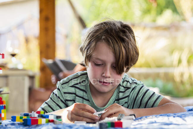 Seven year old boy playing with building blocks on a terrace — Stock Photo
