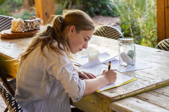 Девочка-подросток пишет на террасе на закате. — стоковое фото