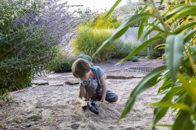 7-річний хлопчик грає в піщаному саду зі своїм іграшковим кораблем.. — стокове фото