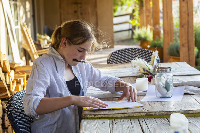 Teenage girl writing outside on terrace at sunset. — Stock Photo