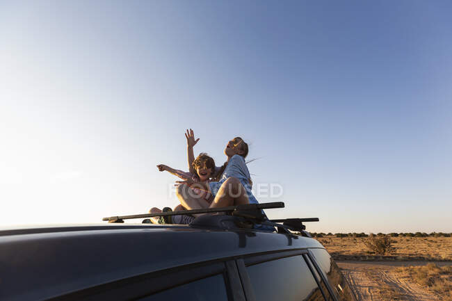 Девочка-подросток и ее младший брат на внедорожнике на пустынной дороге, Бассейн Гасео, Санта-Фе, штат Нью-Мексико. — стоковое фото
