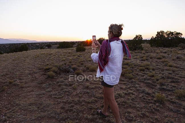 Adult woman photographing sunset on her smart phone. — Stock Photo
