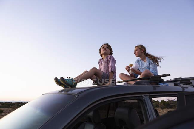 Підліток та її молодший брат під час заходу сонця сидять на машині позашляховика.. — стокове фото