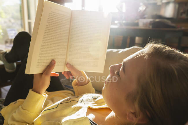 Teenage girl reading book at home in early morning light — Stock Photo