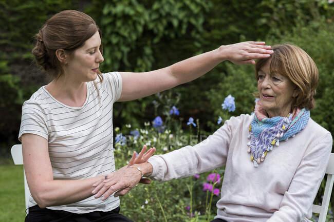 Психотерапевт Рейкі з клієнтом під час сеансу терапії торкається меридіана.. — стокове фото