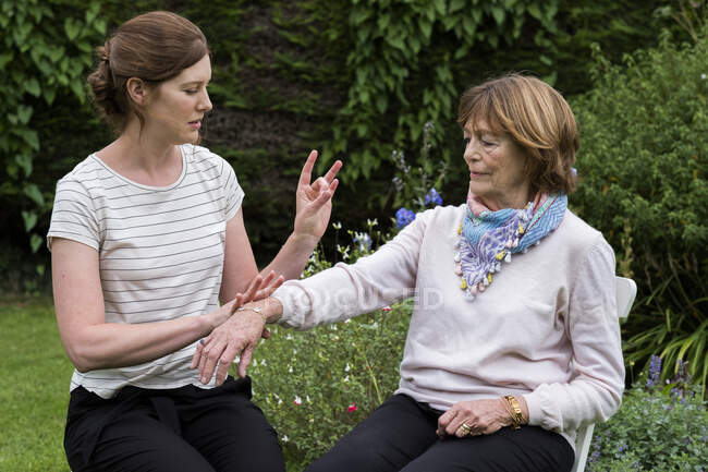 Woman and female therapist at an alternative therapy session in a garden. — Stock Photo