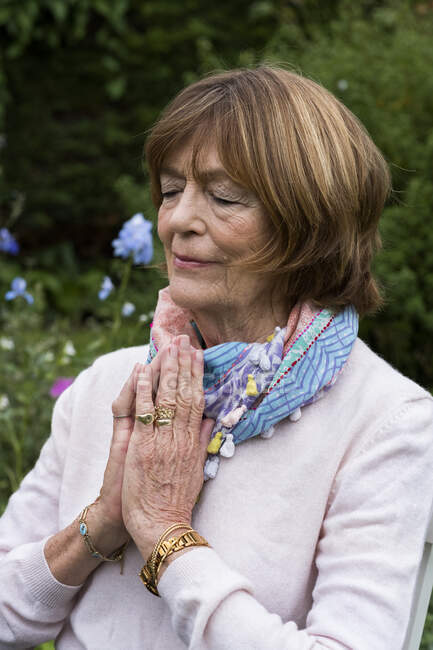 Frau mit geschlossenen Händen und geschlossenen Augen im Garten sitzend — Stockfoto