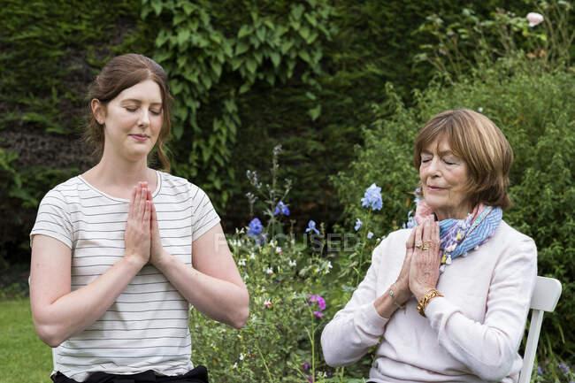 Femme et femme thérapeute assises dans un jardin, les mains ensemble et les yeux fermés. — Photo de stock