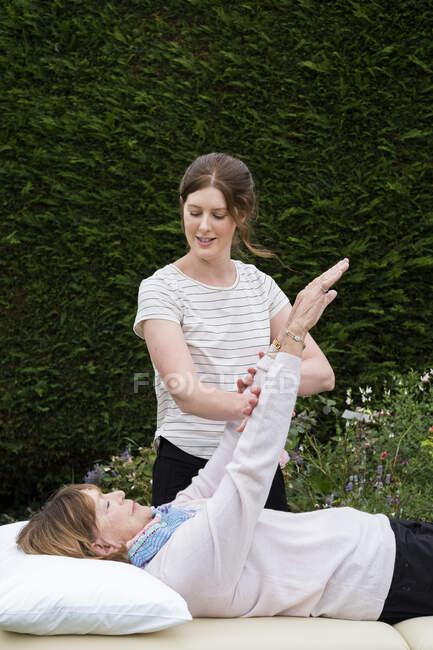 Рейки-терапевт с клиентом на сеансе терапии касаются меридианов точек на теле. — стоковое фото