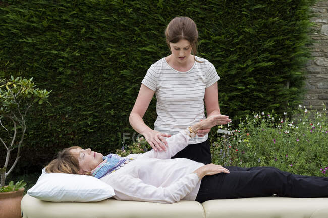 Terapeuta reiki con un cliente in una sessione di terapia che tocca punti meridiani sul corpo. — Foto stock