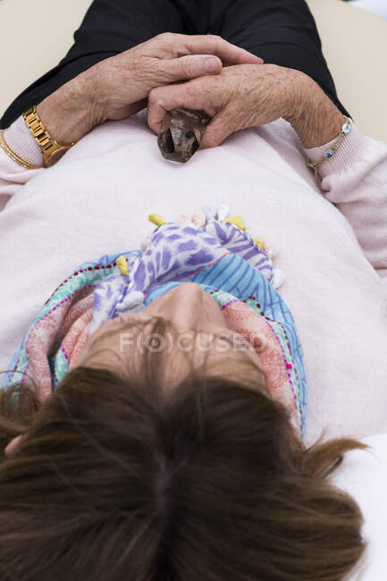Woman holding crystal during alternative therapy session in a garden. — Stock Photo