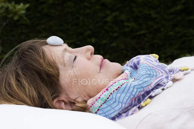 Femme avec de la pierre sur le front pendant une séance de thérapie alternative dans un jardin. — Photo de stock