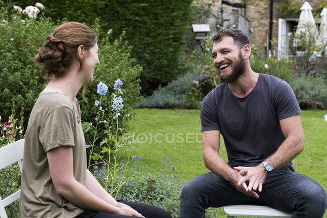 Uomo e terapeuta seduti in giardino, a parlare. — Foto stock
