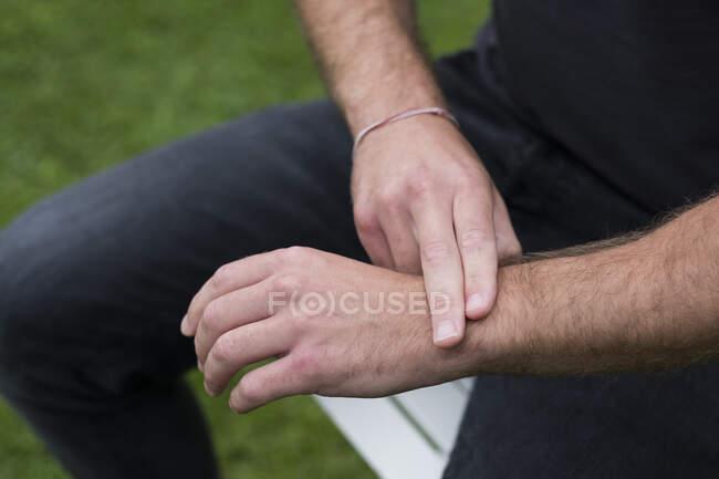 Людина сидить, два пальці на протилежному зап'ясті, ЕФТ зворушлива терапія — стокове фото
