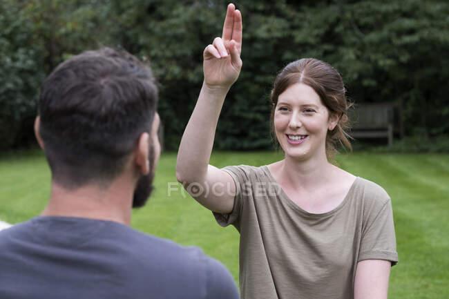 Терапевт и клиент, сидящий в саду, женщина с поднятой рукой и двумя вытянутыми пальцами. — стоковое фото