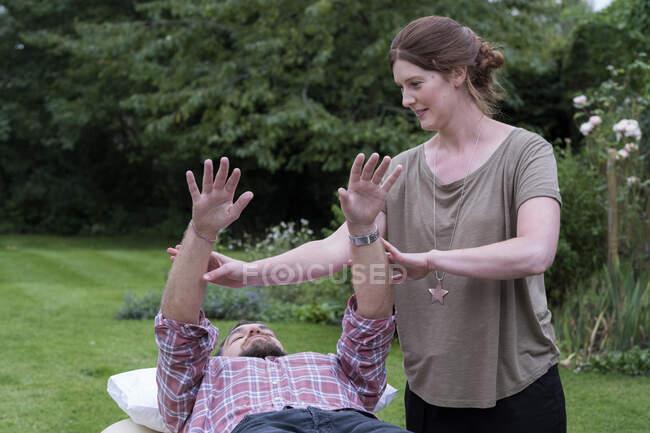 Hombre en un sofá y terapeuta levantando los brazos en una sesión de terapia de jardín - foto de stock