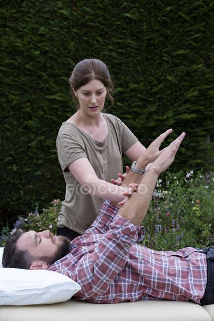 Uomo su un divano e terapeuta alzare le braccia in una sessione di terapia in giardino — Foto stock