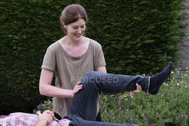 Uomo su un divano e terapeuta alzando la gamba, in una sessione di terapia in giardino — Foto stock