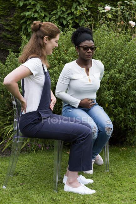 Жінка і жінка-терапевт віддзеркалюють один одного, руки за спину і шлунок. — стокове фото