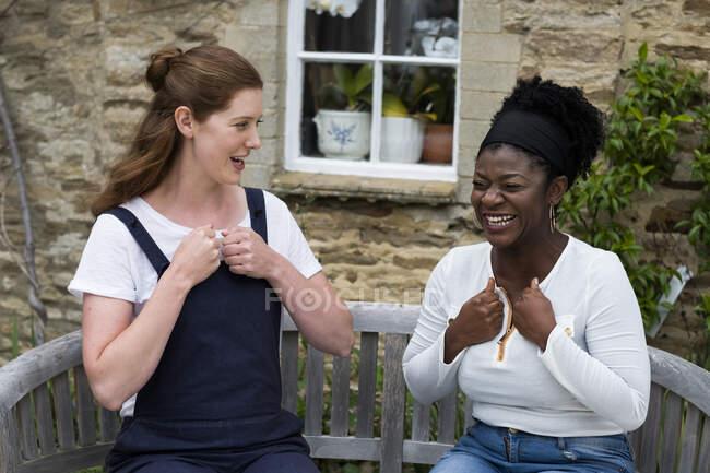 Жінка і жіночий терапевт розмовляють в саду.. — стокове фото