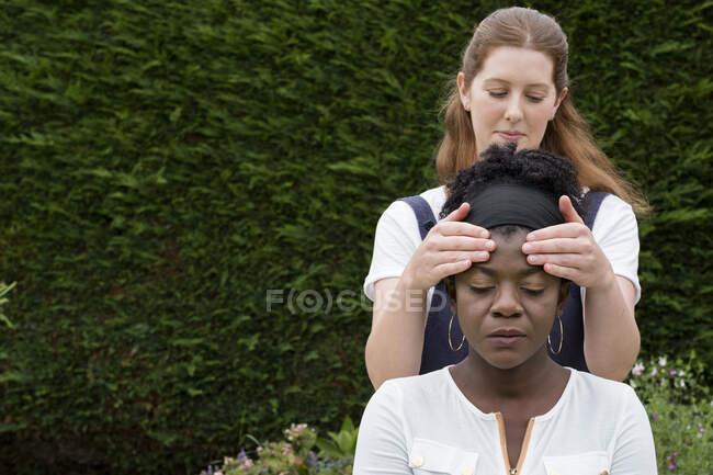 Terapista con le mani sulle tempie di un cliente, sessione di terapia all'aperto — Foto stock