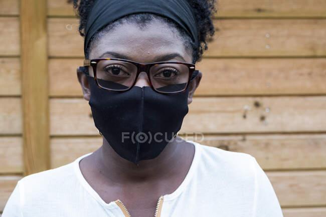 Ritratto di donna nera che indossa occhiali e maschera, guardando la macchina fotografica. — Foto stock