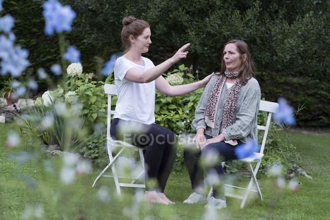 Thérapeute femme et femme assise à une séance de thérapie alternative dans un jardin. — Photo de stock