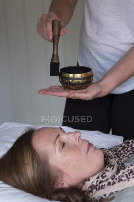 Donna su un divano, e una terapista femminile che usa la ciotola tibetana per cantare, la terapia del suono — Foto stock