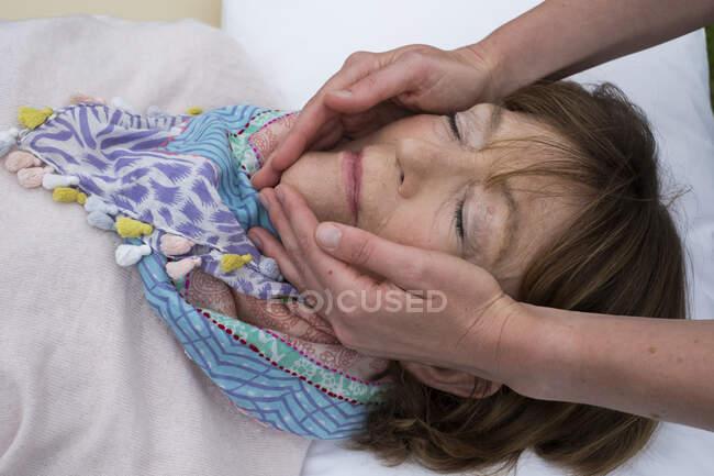 Terapista tenendo le mani su entrambi i lati di un volto cliente. — Foto stock
