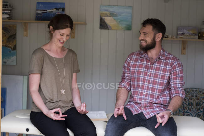 Man and therapist seated with hands in a meditative pose, finger and thumb lightly touching. — Stock Photo