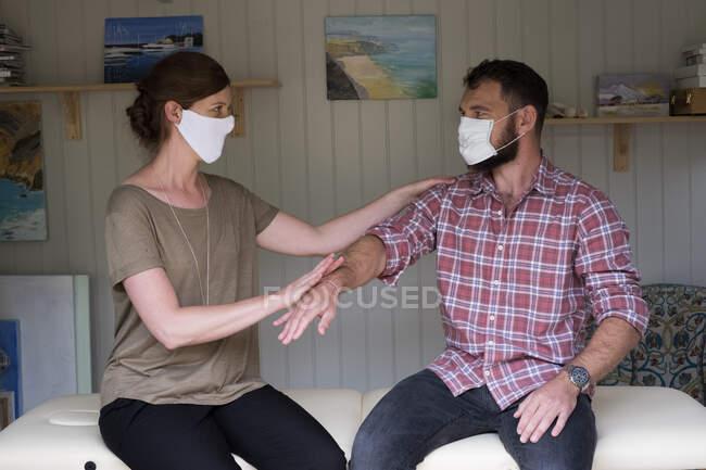 Терапіст і клієнт в масках обличчя, торкаючись простягнутою рукою — стокове фото