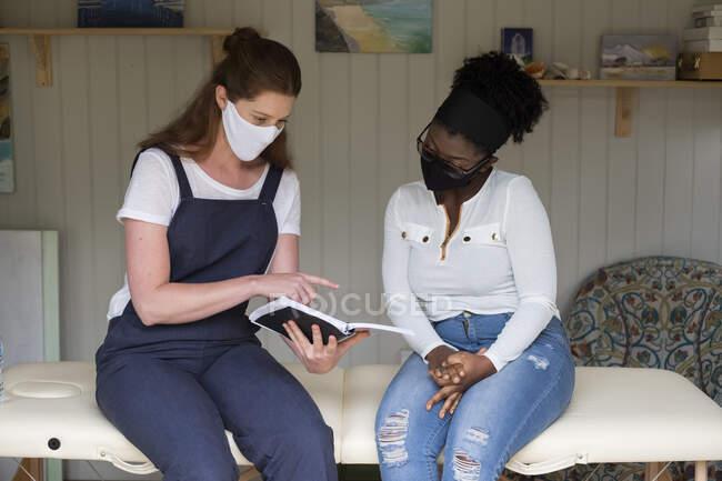 Mulher e terapeuta feminina em máscaras faciais durante uma sessão de terapia. — Fotografia de Stock