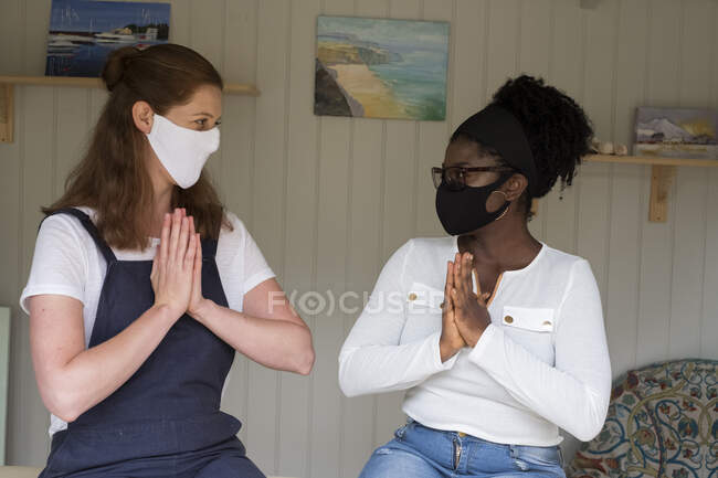 Alternative therapy session, practitioner and client, women in face masks with hands together. — Stock Photo