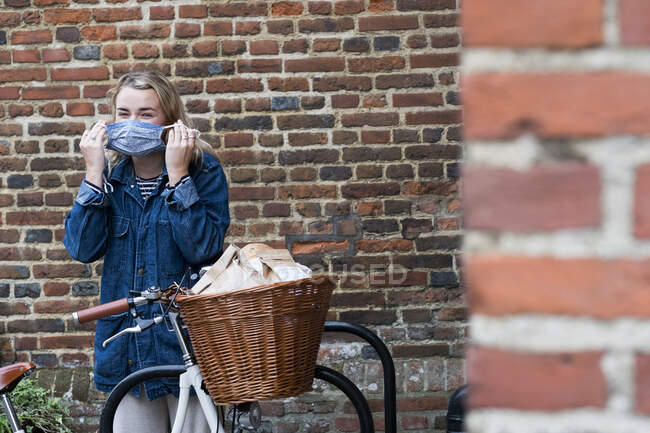 Young blond woman standing next to bicycle with basket, putting on face mask. — Stock Photo