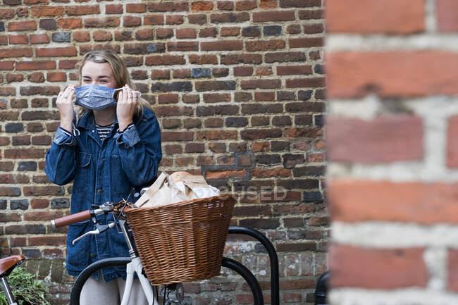 Молодая блондинка стоит рядом с велосипедом с корзиной, надевая маску для лица. — стоковое фото