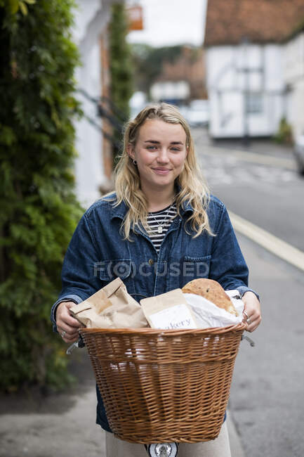 Young blond woman on bicycle with basket, smiling at camera. — Stock Photo