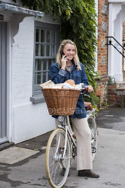 Молодая блондинка на велосипеде с корзиной, разговаривает по мобильному телефону. — стоковое фото