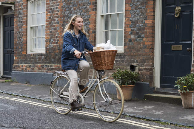 Молодая блондинка едет по деревенской улице. — стоковое фото